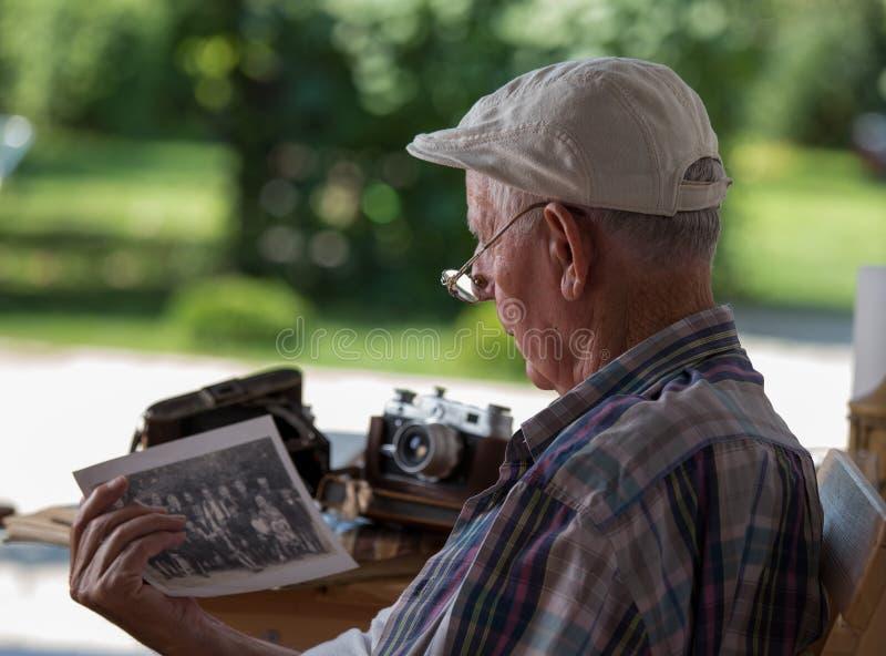 Hogere mens die oude foto's bekijken stock foto's