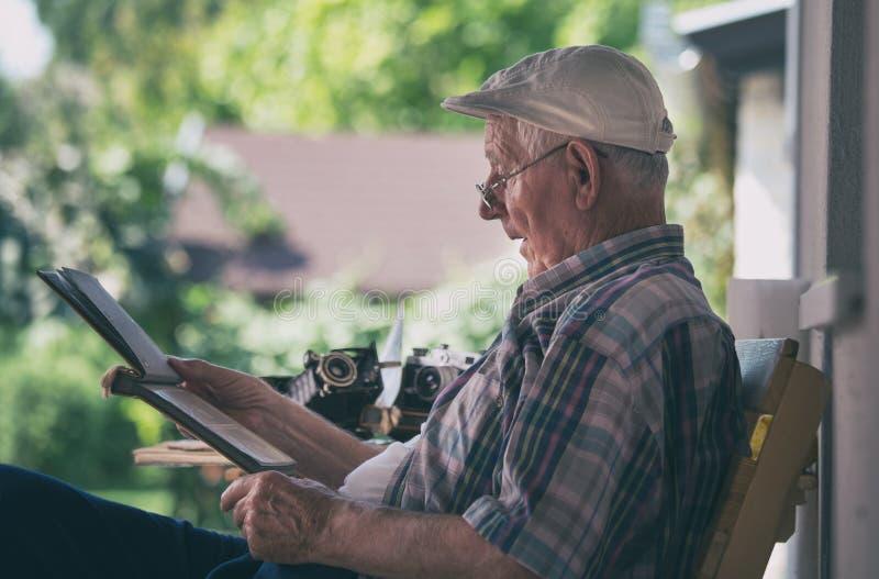 Hogere mens die oude foto's bekijken stock fotografie
