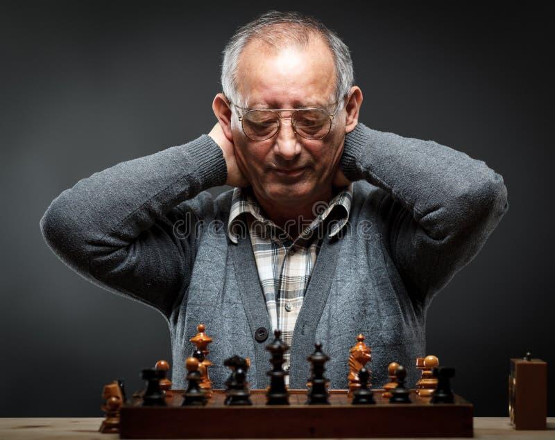 Hogere mens die over zijn volgende beweging in een spel van schaak denken stock foto's