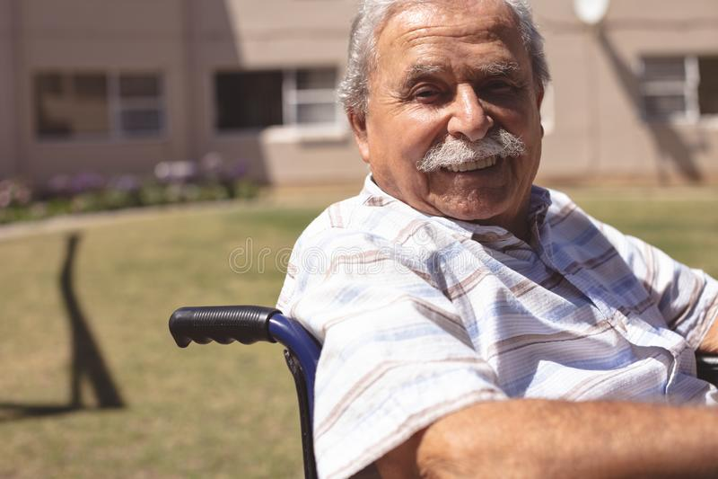 Hogere mens die in rolstoel bij de camera glimlachen royalty-vrije stock afbeelding