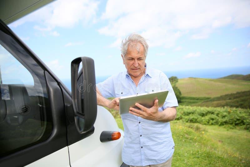 Hogere mens die tablet gebruiken door het kamperen auto stock afbeelding