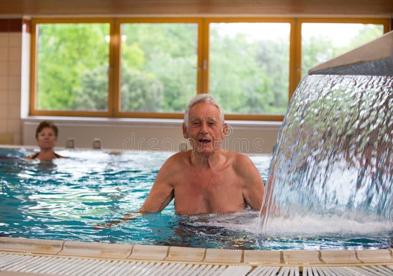 Hogere mens die van douche in pool genieten stock fotografie