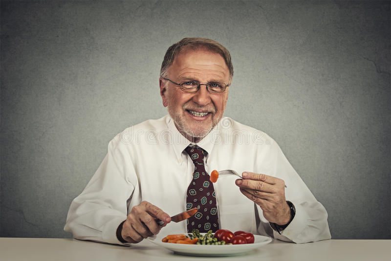 Hogere mens die verse groentesalade eten royalty-vrije stock foto