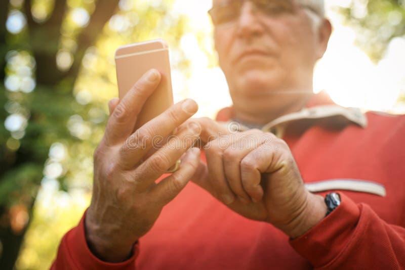 Hogere mens die zich in bos en gebruikende slimme telefoon bevinden FO stock afbeeldingen