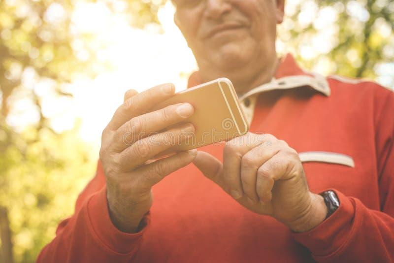 Hogere mens die zich in bos en gebruikende slimme telefoon bevinden Foc stock foto's