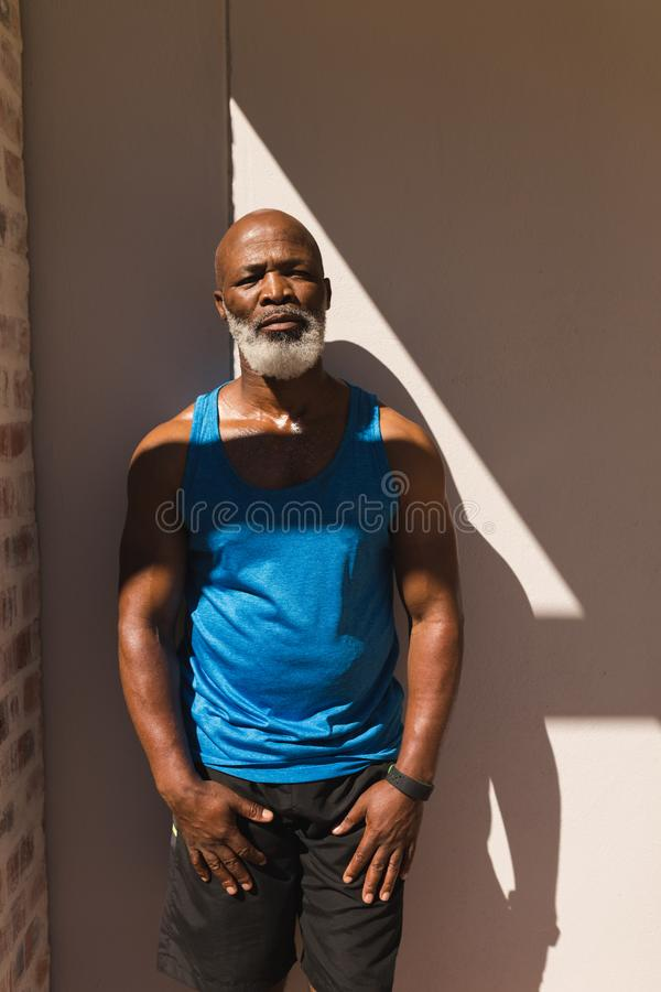 Hogere mens die zich tegen muur in de binnenplaats van huis bevinden royalty-vrije stock foto