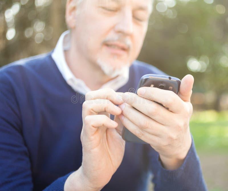 Hogere mens die zijn celtelefoon met behulp van stock foto