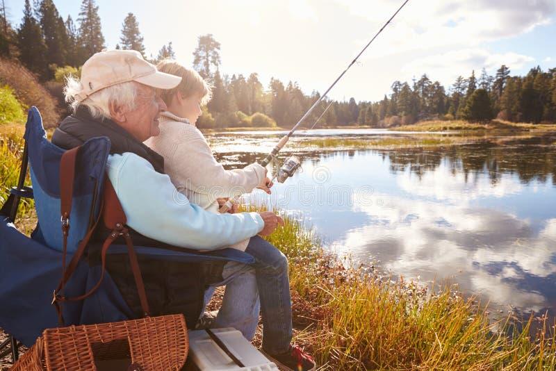 Hogere mens die zijn kleinzoon onderwijzen om bij een meer te vissen stock foto