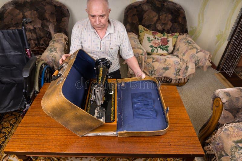 Hogere Mens die zijn Naaimachine in een Geval zetten stock foto's