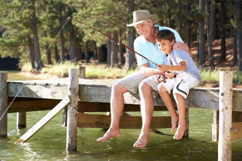 Hogere mens en kleinzoon visserij stock afbeelding