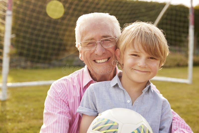 Hogere mens en kleinzoonholdingsbal die bij camera glimlachen royalty-vrije stock afbeelding