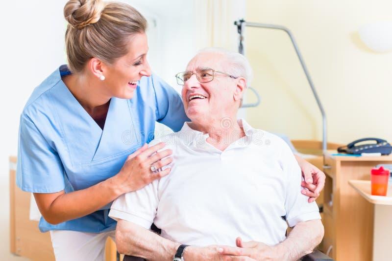 Hogere mens en oude dagverpleegster in verpleeghuis stock foto's