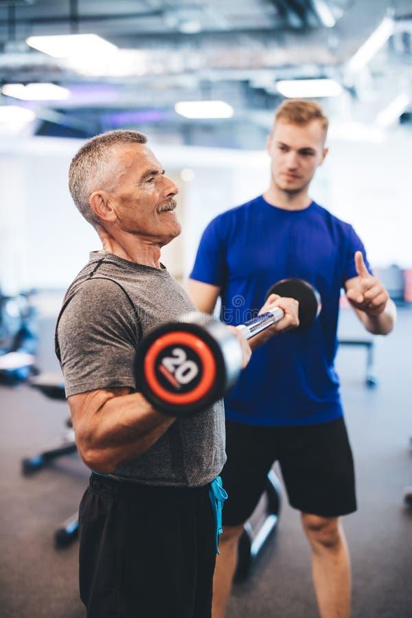 Hogere mens en persoonlijke trainer bij de gymnastiek stock foto's