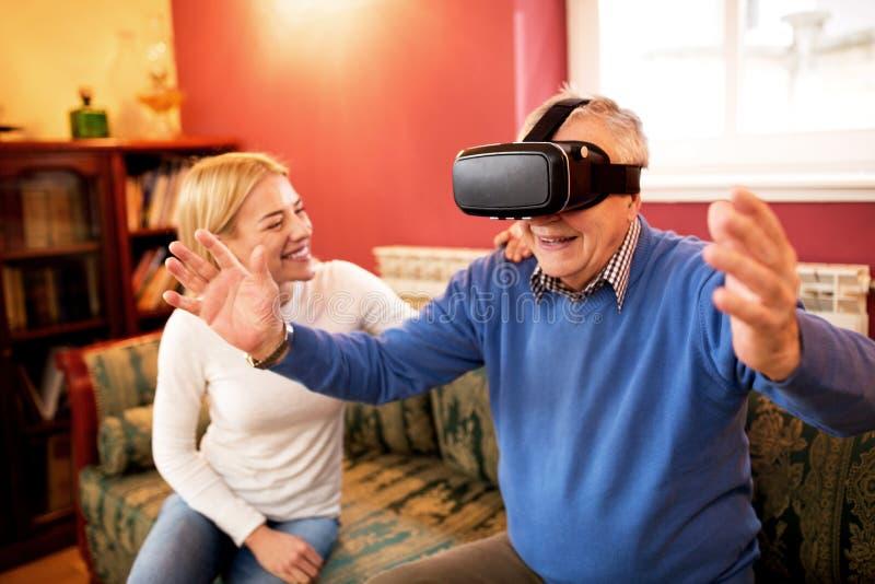 Hogere mens gebruikend virtuele werkelijkheidssimulator en hebbend pret met n stock afbeeldingen