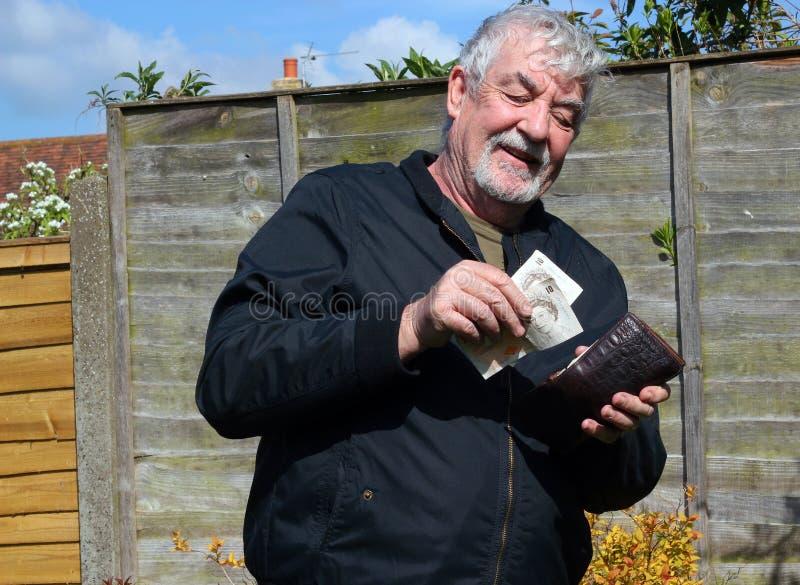 Hogere mens gelukkig om geld in zijn portefeuille te zetten royalty-vrije stock foto's