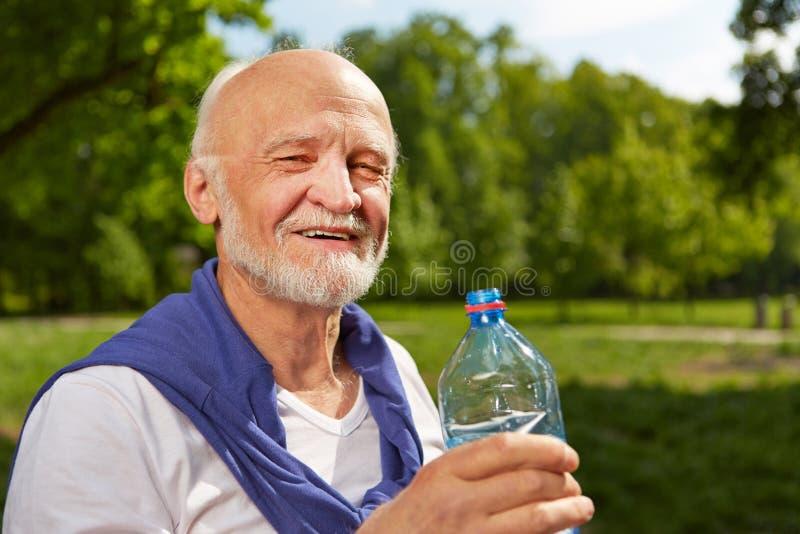 Hogere mens het drinken fles water in de zomer stock afbeelding