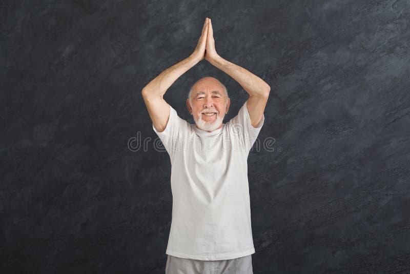 Hogere mens het praktizeren yoga die zich in padmasana bevinden stock fotografie