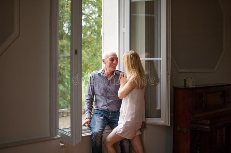 Hogere Mens in Jeans en Overhemd die Zijn Jonge Blonde Vrouw koesteren die zich dichtbij het Venster in Hun Huis tijdens de Zomer royalty-vrije stock foto