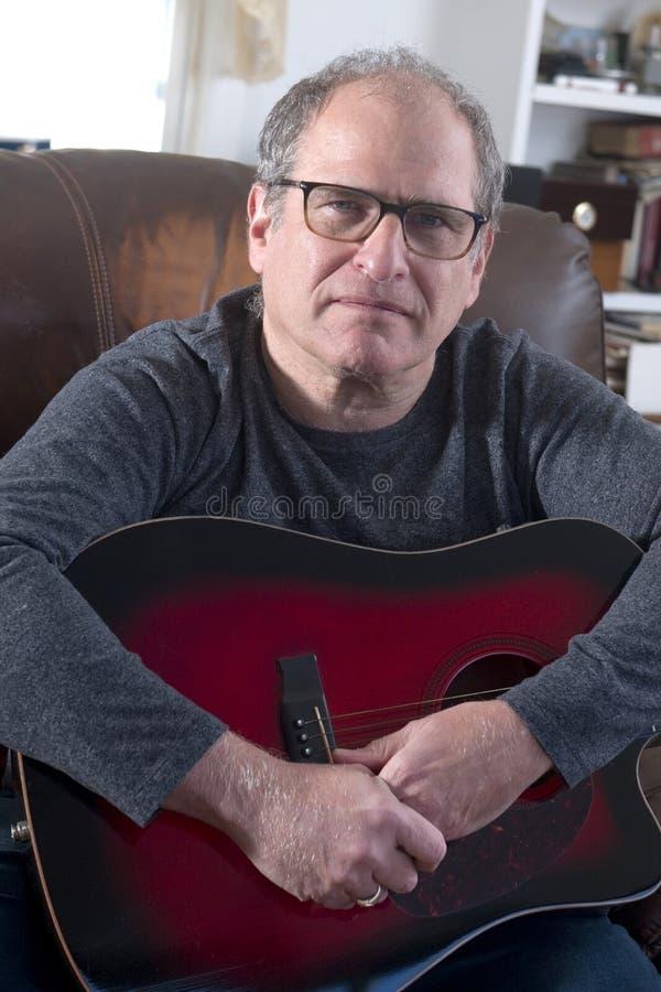 Hogere mens met akoestische gitaar stock foto's