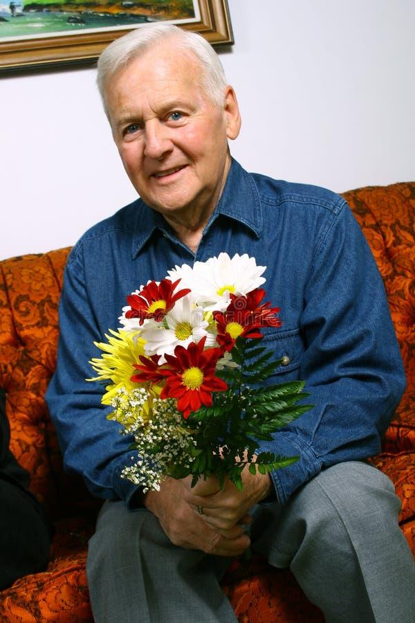 Hogere mens met bloemen royalty-vrije stock afbeeldingen