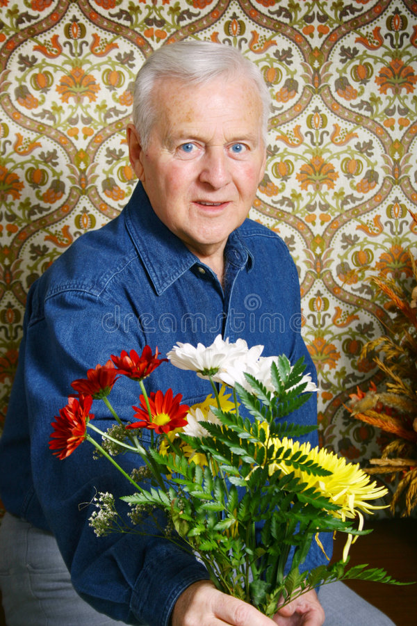 Hogere mens met bloemen stock foto