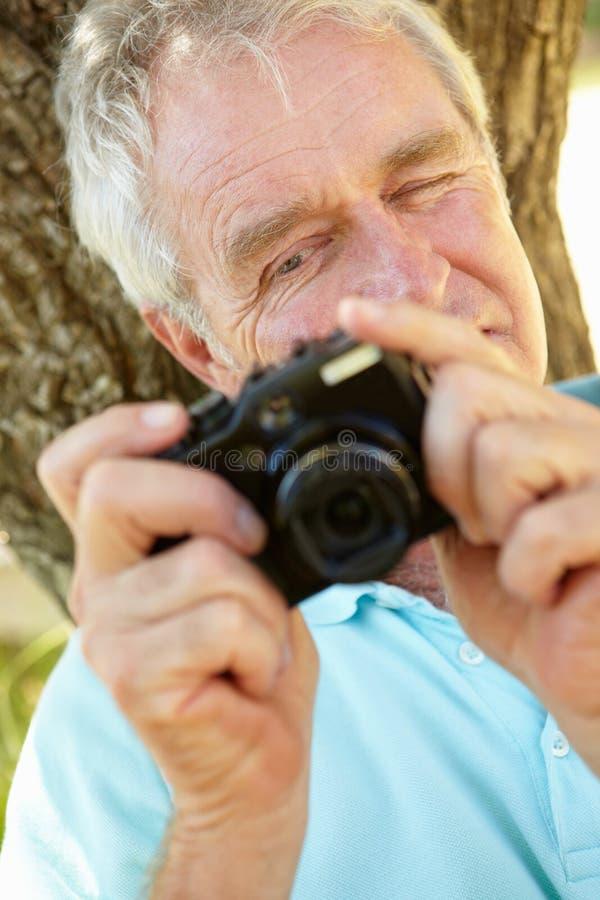 Hogere mens met camera het glimlachen stock afbeeldingen