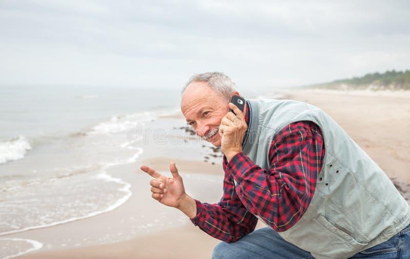 Hogere mens met een telefoon op overzeese achtergrond royalty-vrije stock afbeelding