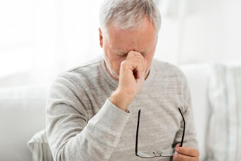 Hogere mens met het hebben van hoofdpijn stock foto