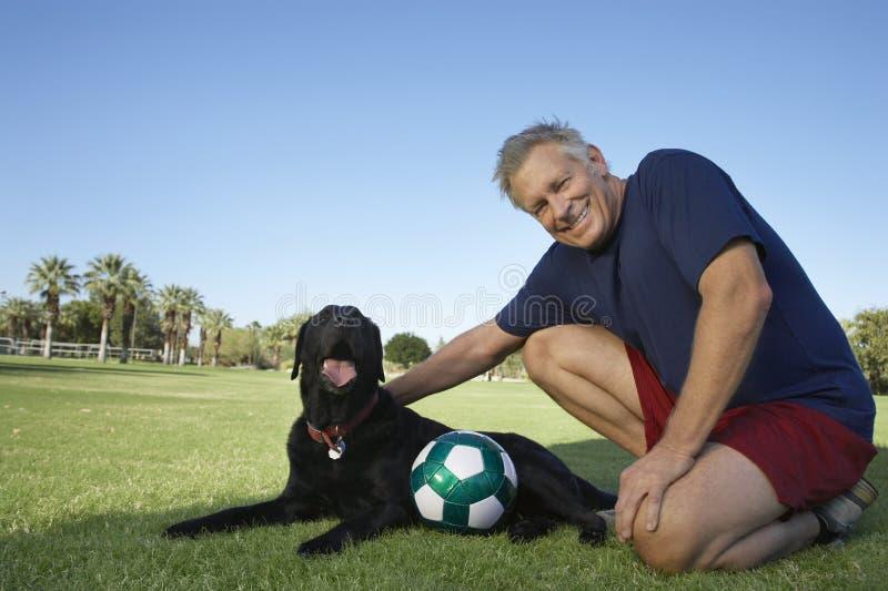 Hogere Mens met Hond en Voetbalbal in Park stock afbeelding