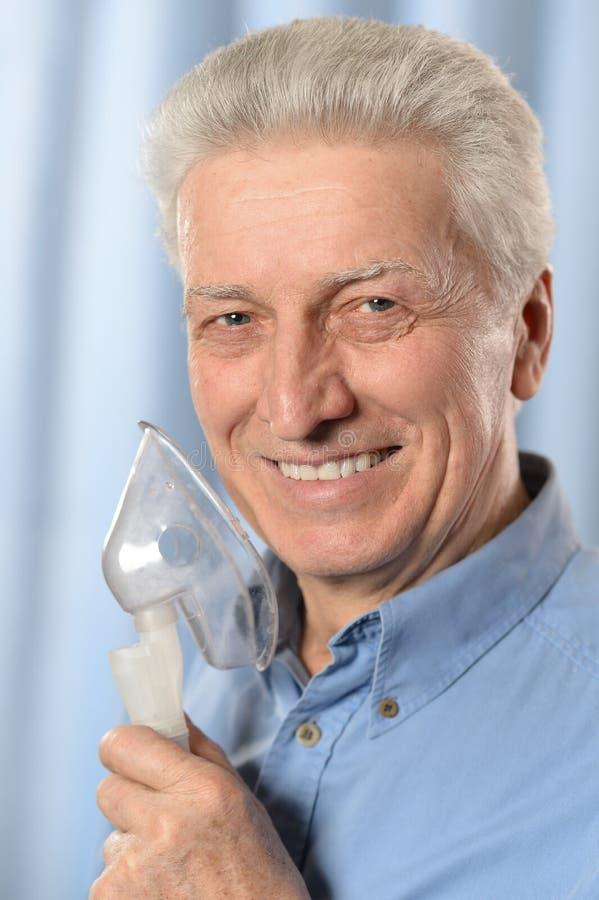 Hogere mens met inhaleertoestel stock foto
