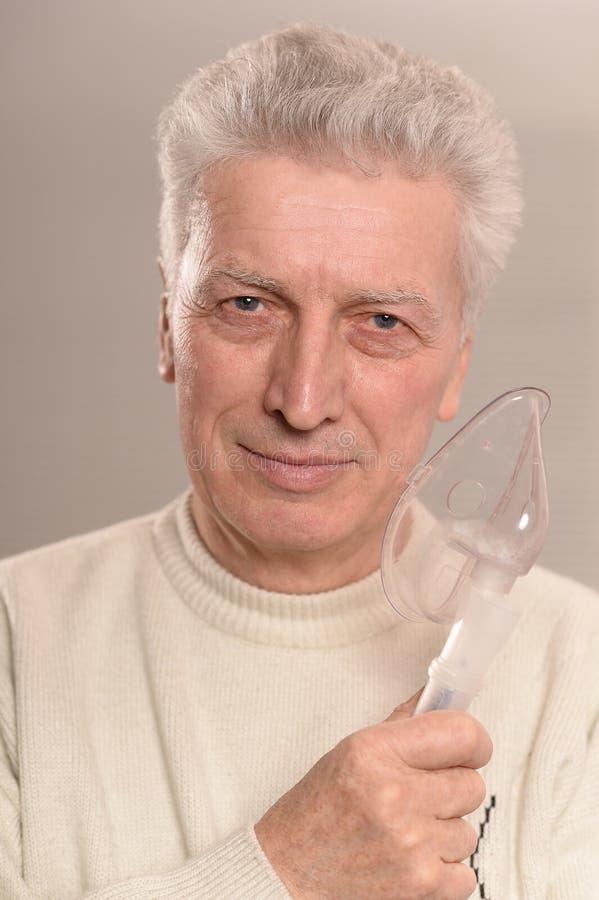 Hogere mens met inhaleertoestel stock foto's