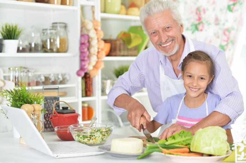 Hogere mens met kleindochter die diner in keuken voorbereiden royalty-vrije stock fotografie