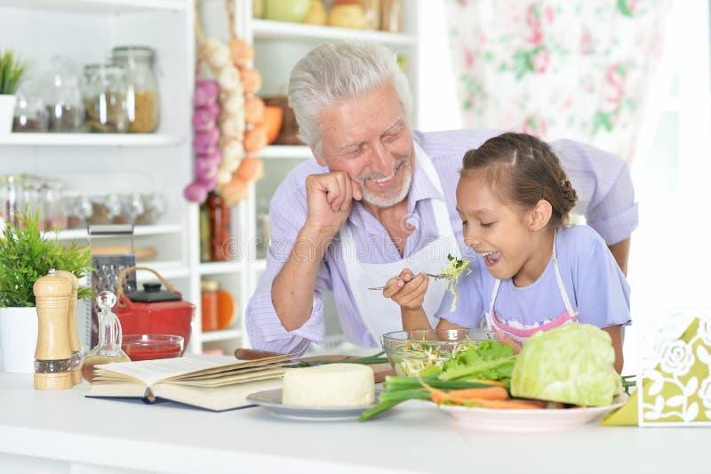 Hogere mens met kleindochter die diner in keuken voorbereiden stock fotografie