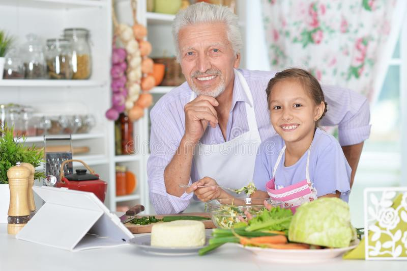 Hogere mens met kleindochter die diner in keuken voorbereiden stock foto