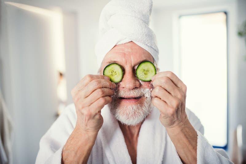 Hogere mens met komkommer op voorzijde van zijn ogen in badkamers binnen thuis royalty-vrije stock afbeeldingen