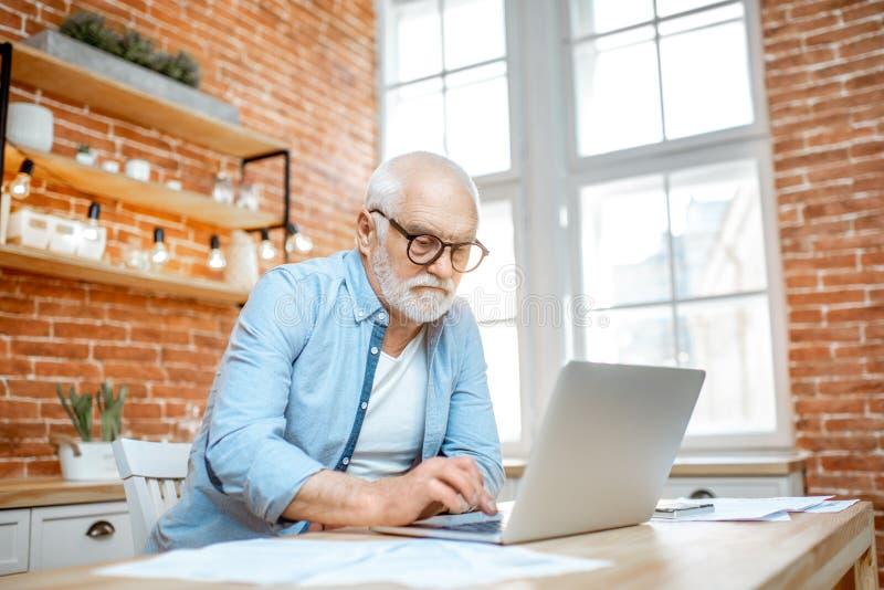 Hogere mens met laptop thuis royalty-vrije stock foto's