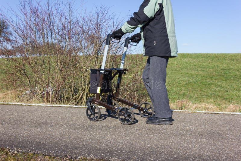 hogere mens met rollator op een bikeway en zonnige de winterdag royalty-vrije stock fotografie