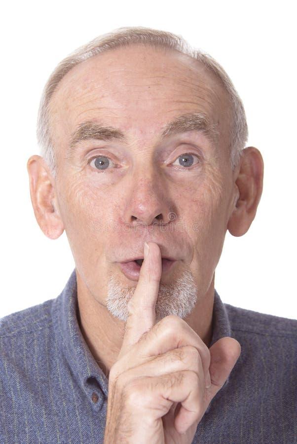 Hogere mens met vinger aan lippen stock fotografie