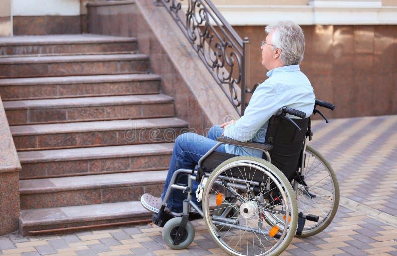 Hogere mens in rolstoel dichtbij treden in openlucht stock afbeeldingen