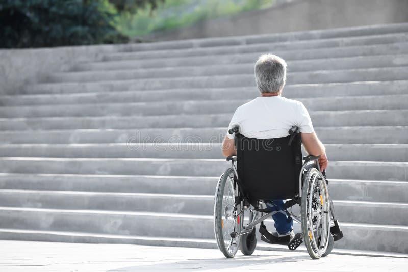 Hogere mens in rolstoel dichtbij treden in openlucht royalty-vrije stock afbeeldingen