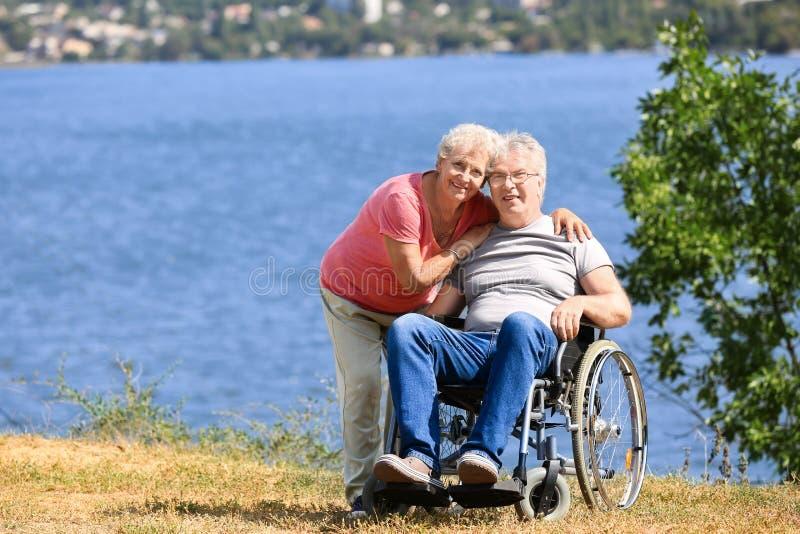 Hogere mens in rolstoel en zijn vrouw dichtbij rivier royalty-vrije stock afbeeldingen
