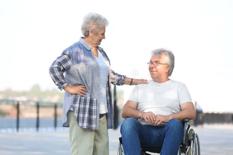 Hogere mens in rolstoel en zijn vrouw in openlucht stock afbeelding