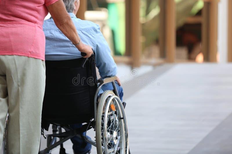 Hogere mens in rolstoel en zijn vrouwenoprit in openlucht stock afbeeldingen