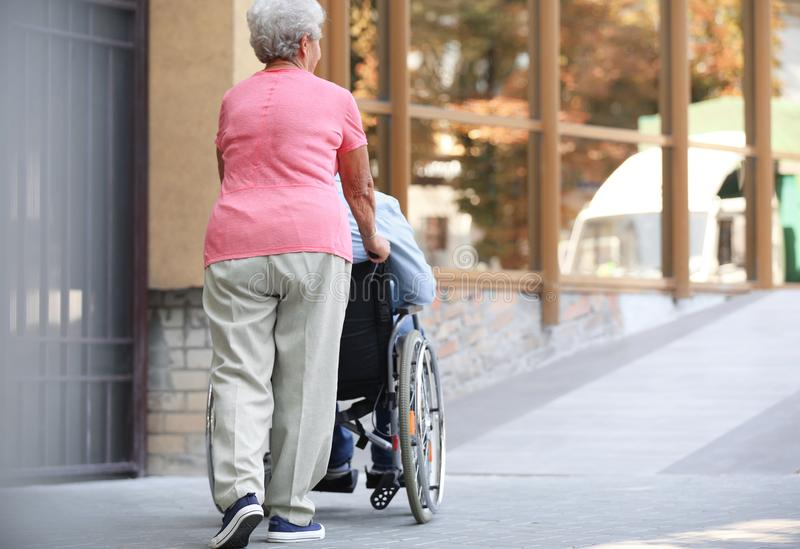 Hogere mens in rolstoel en zijn vrouwenoprit in openlucht royalty-vrije stock foto
