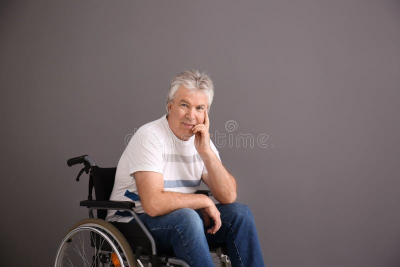 Hogere mens in rolstoel op grijze achtergrond royalty-vrije stock foto's