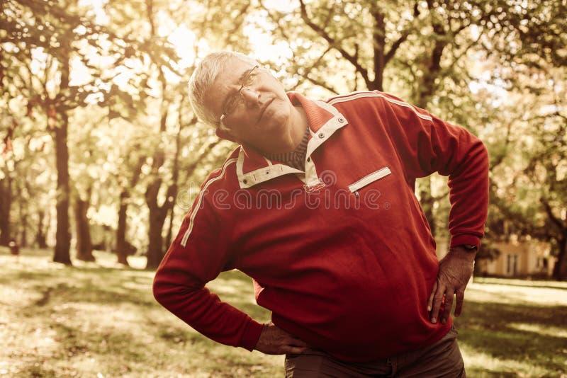Hogere mens in sporten die het uitoefenen in park kleden stock foto's