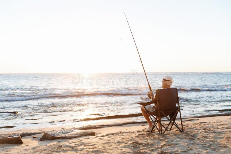 Hogere mens visserij op zee kant stock foto