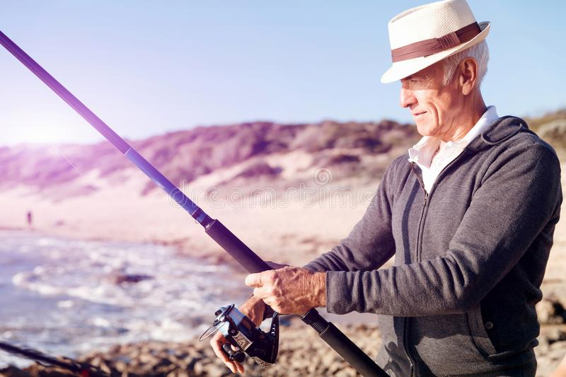 Hogere mens visserij op zee kant royalty-vrije stock fotografie