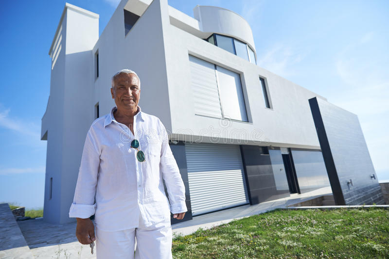 Hogere mens voor modern huis stock foto