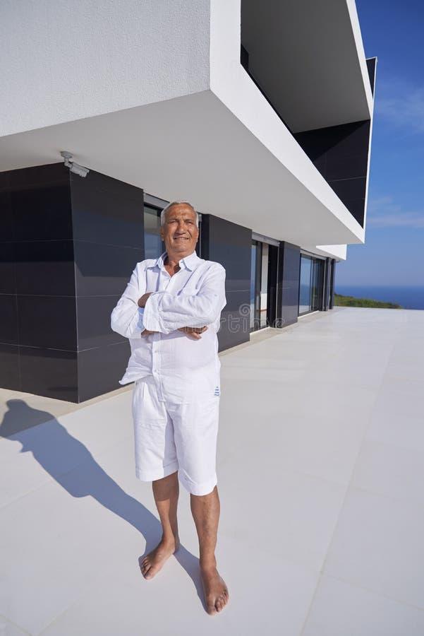 Hogere mens voor modern huis royalty-vrije stock foto's